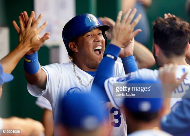 Catcher Salvador Perez of the Kansas City Royals is congratulated by teammates in the dugout after scoring during the 3rd inning of the game against...