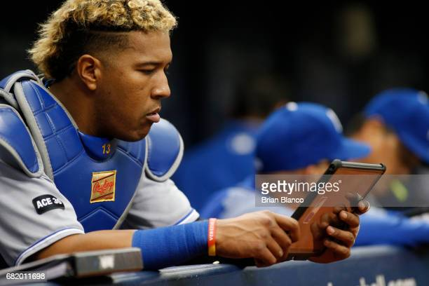 Catcher Salvador Perez of the Kansas City Royals reviews a tablet in the dugout during the seventh inning of a game against the Tampa Bay Rays on May...