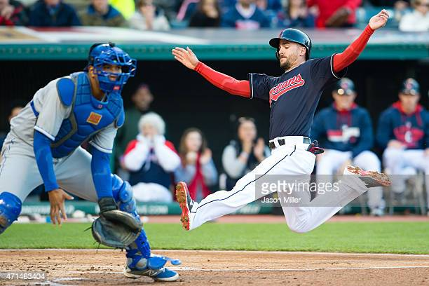 Catcher Salvador Perez of the Kansas City Royals waits for the throw as Lonnie Chisenhall of the Cleveland Indians is safe at home on a hit from...