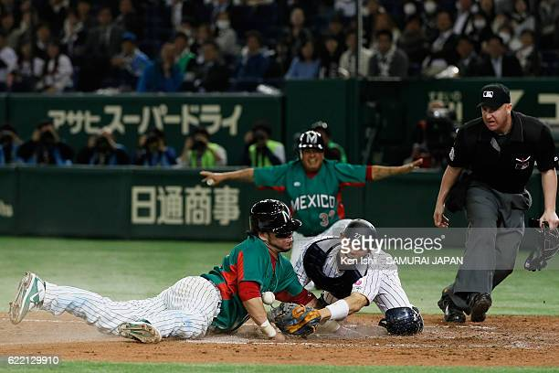 Catcher Sebastian Valle of Mexico slides safely into the home base to score as Catcher Shota Ohno of Japan fails to tag in the sixth inning during...