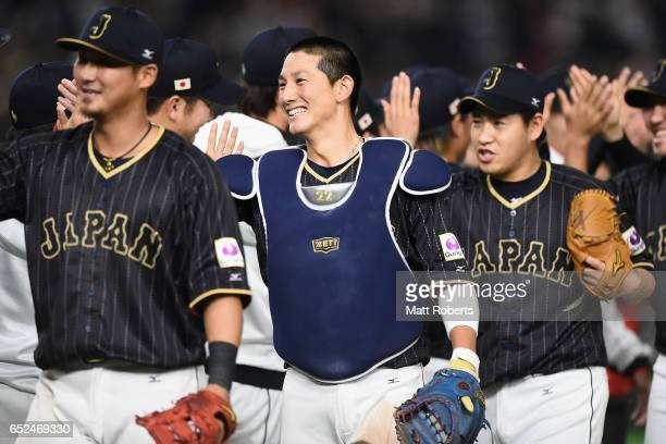Catcher Seiji Kobayashi and Japanese players celebrate after their 86 victory in the World Baseball Classic Pool E Game Two between Japan and...