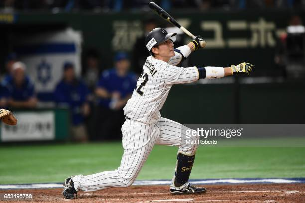Catcher Seiji Kobayashi of Japan flies out in the bottom of the fourth inning during the World Baseball Classic Pool E Game Six between Israel and...