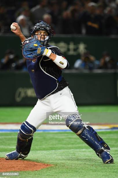 Catcher Seiji Kobayashi of Japan throws to the first base in the bottom of the seventh inning during the World Baseball Classic Pool B Game Three...