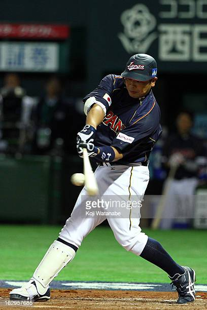 Catcher Shinnosuke Abe of Japan hits a RBI single in the top half of the eighth inning during the World Baseball Classic First Round Group A game...