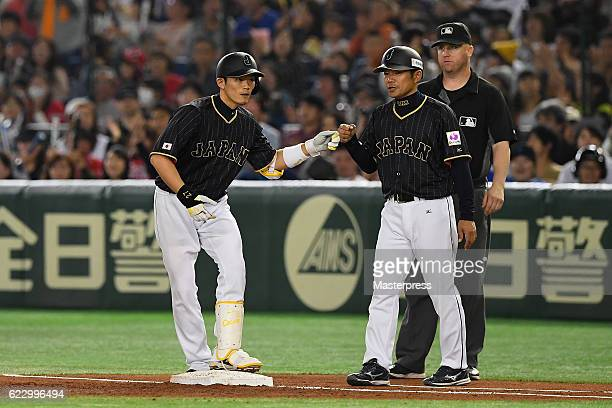 Catcher Shota Ohno of Japan is congratulated by Coach Toshinori Nishi of Japan after hitting a RBI single in the second inning during the...
