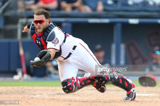 Catcher Spencer Kieboom of the Washington Nationals dives to make a catch on a bunt pop up off the bat of Pedro Florimon of the Atlanta Braves in the...
