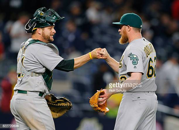 Catcher Stephen Vogt of the Oakland Athletics congratulates closer Sean Doolittle after getting the final out in the ninth inning defeating the New...
