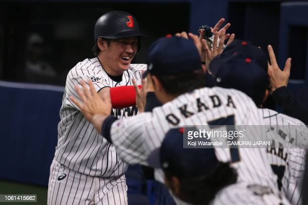 Catcher Takuya Kai of Japan is congratulated by his team mates after hitting a RBI double to make it 56 in the bottom of 8th inning during the game...