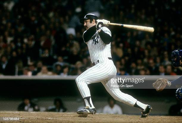 Catcher Thurman Munson of the New York Yankees swings and watches the flight of his ball against the Kansas City Royals during a MLB baseball game...