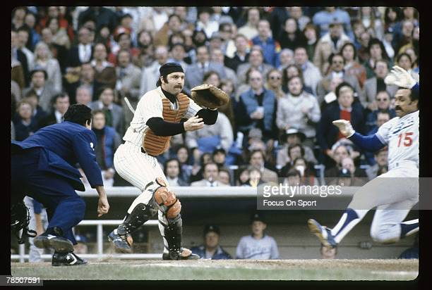 Catcher Thurman Munson of the New York Yankees waits on the ball as Davey Lopes of the Los Angeles Dodgers slides in safe at home-plate during the...