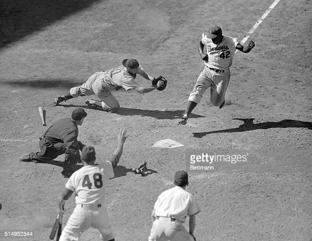 Catcher Toby Atwell scrambles for Dodger second baseman Jackie Robinson, who crosses home plate to score the winning run in the last half of the...