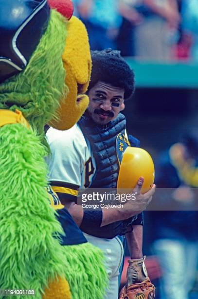 Catcher Tony Pena of the Pittsburgh Pirates looks at team mascot Pirate Parrot before the start of a Major League Baseball game at Three Rivers...