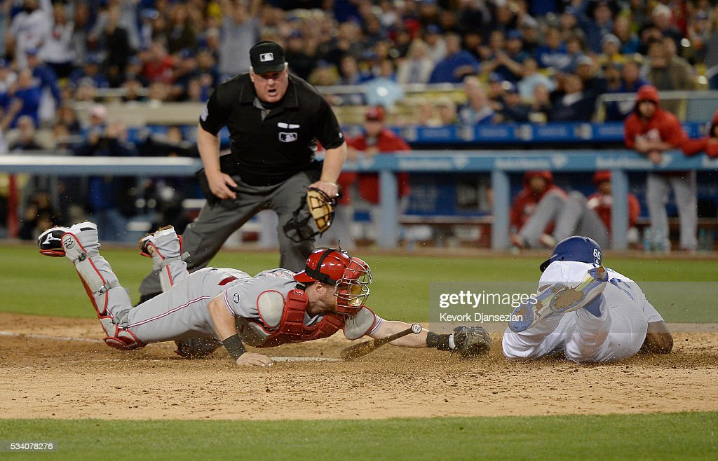 Catcher Tucker Barnhart #16 of the Cincinnati Reds attempts to tag out Yasiel Puig #66 of the Los Angeles Dodgers as he scores a run with home plate umpire Bill Miller #26 looking on during the sixth inning of the baseball game at Dodger Stadium May 24, 2016, in Los Angeles, California.