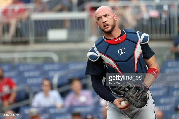 Catcher Tyler Flowers of the Atlanta Braves looks on after catching a foul ball hit by Trea Turner of the Washington Nationals for the first out of...