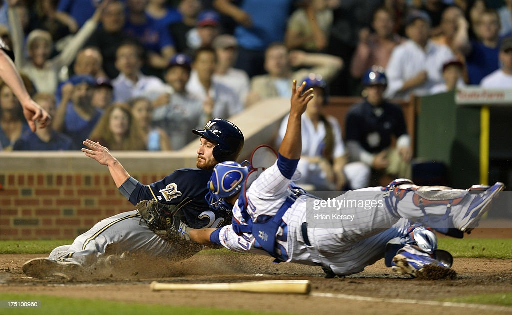 Catcher Welington Castillo #53 of the Chicago Cubs (R) tags out Jonathan Lucroy #20 of the Milwaukee Brewers at home plate after Lucroy tried to score from second base on a single hit by Caleb Gindl #15 during the fourth inning at Wrigley Field on July 31, 2013 in Chicago, Illinois.