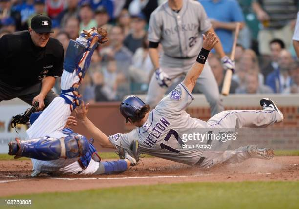 Catcher Welington Castillo of the Chicago Cubs tags out Todd Helton of the Colorado Rockies at home plate after he tried to score on a single hit by...