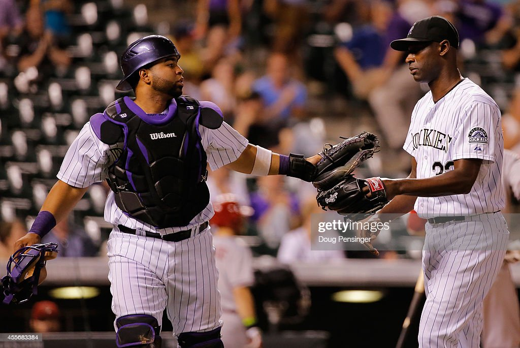Catcher Wilin Rosario #20 and closer LaTroy Hawkins #32 of the Colorado Rockies leave the field after Rosario caught a pop foul by Jake Lamb #19 of the Arizona Diamondbacks to end the top of the ninth inning at Coors Field on September 18, 2014 in Denver, Colorado. Hawkins went on to earn the win as Rosario hit a two run walk off home run as they Rockies defeated the Diamondbacks 7-6.