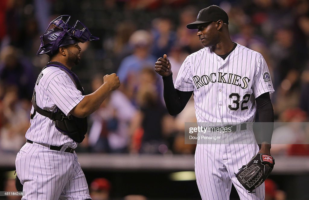 Catcher Wilin Rosario #20 and relief pitcher LaTroy Hawkins #32 of the Colorado Rockies celebrate their 10-5 victory over the St. Louis Cardinals at Coors Field on June 24, 2014 in Denver, Colorado.
