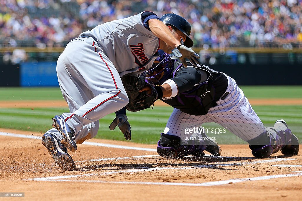 Catcher Wilin Rosario #20 of the Colorado Rockies tags out Brian Dozier #2 of the Minnesota Twins for the second out of the first inning at Coors Field on July 13, 2014 in Denver, Colorado.