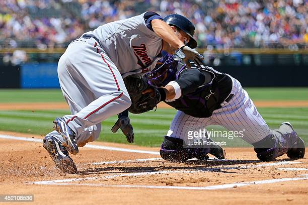 Catcher Wilin Rosario of the Colorado Rockies tags out Brian Dozier of the Minnesota Twins for the second out of the first inning at Coors Field on...