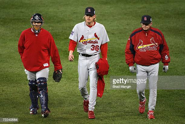 Catcher Yadier Molina starting pitcher Jeff Weaver and pitching coach Dave Duncan of the St Louis Cardinals walk across the outfield before the start...