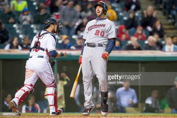 Catcher Yan Gomes of the Cleveland Indians runs off the field as Chris Colabello of the Minnesota Twins reacts to striking out to end the top of the...