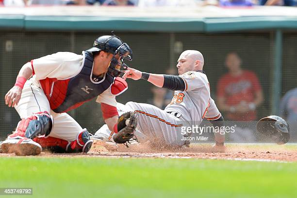 Catcher Yan Gomes of the Cleveland Indians tries t make the tag as Steve Pearce of the Baltimore Orioles scores during the sixth inning at...