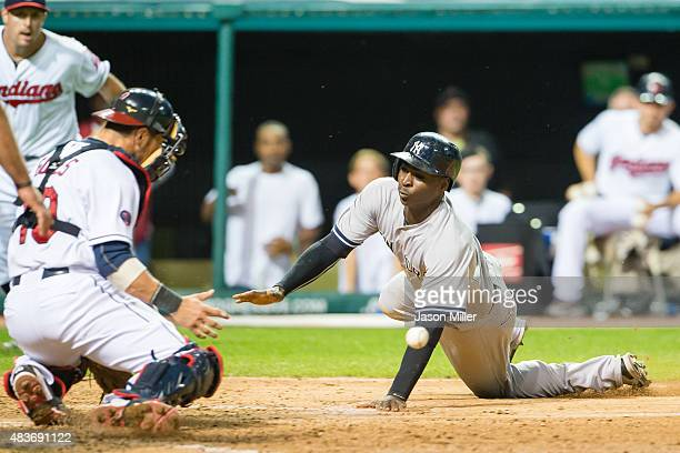 Catcher Yan Gomes of the Cleveland Indians tries to make the play as Didi Gregorius of the New York Yankees scores on a single by Chase Headley in...