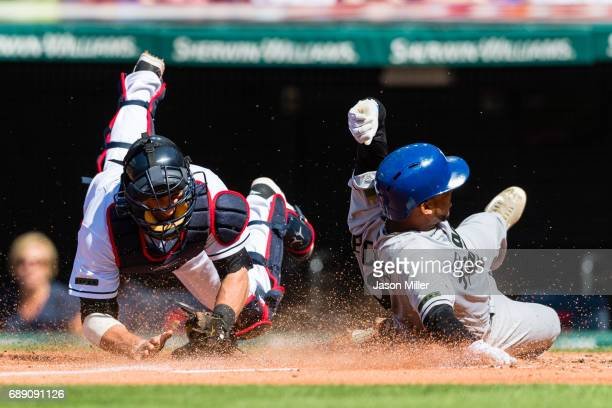 Catcher Yan Gomes of the Cleveland Indians tries to tag Alcides Escobar of the Kansas City Royals as he scores on a sacrifice fly by Salvador Perez...