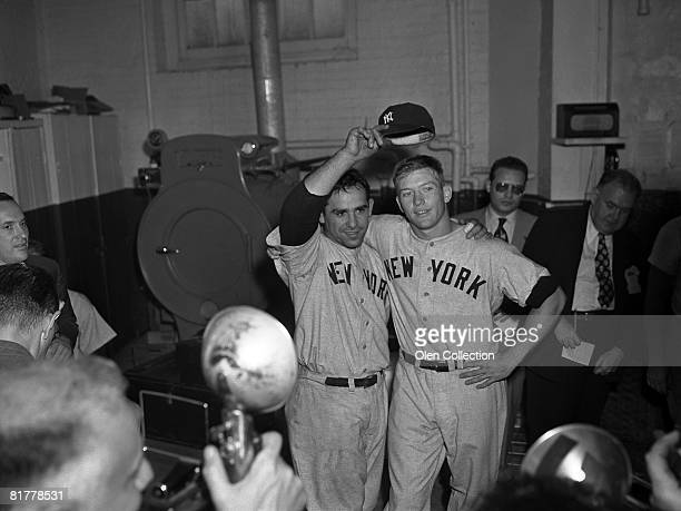 Catcher Yogi Berra and outfielder Mickey Mantle of the New York Yankees pose together in the clubhouse after a World Series game in October 1956...