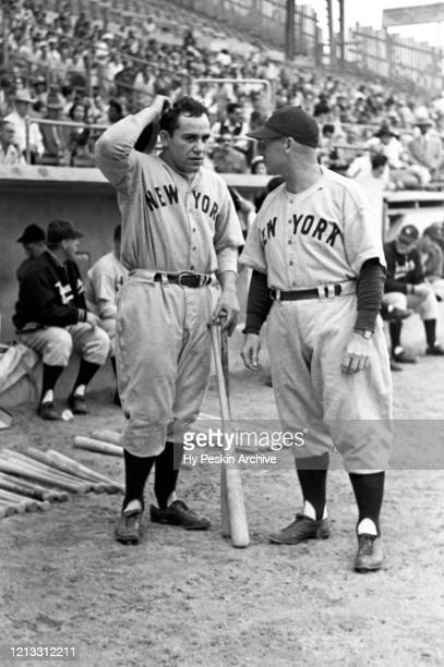 Catcher Yogi Berra of the New York Yankees talks to his coach Charlie Dressen before batting during an MLB Spring Training game against the Brooklyn...
