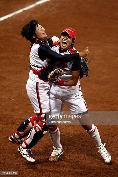 Catcher Yukiyo Mine and Yukiko Ueno of Japan celebrate Japan's 31 win against the United States during the women's grand final gold medal softball...