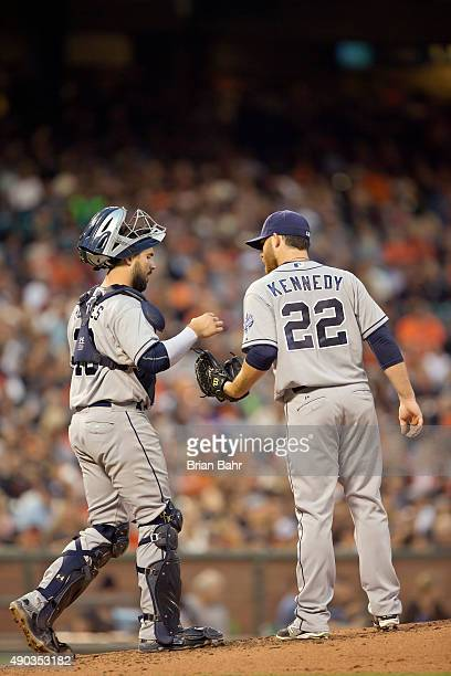 Catchers Austin Hedges hands the ball back to starting pitcher Ian Kennedy of the San Diego Padres after giving up two walks with two outs to the San...