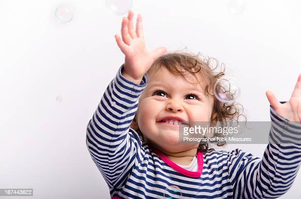 catching bubbles - arms raised stock photos and pictures