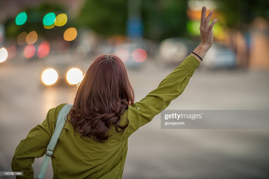 Catching the attention of a passing taxi cab : Stock Photo