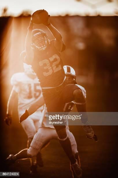 den ball fängt, während american-football-spiels! - football receiver stock-fotos und bilder