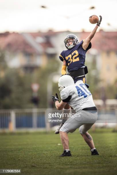 catching the ball on american football match! - wide receiver athlete stock photos and pictures