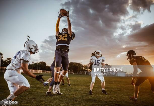 fangen sie den ball auf american-football-spiel! - football receiver stock-fotos und bilder