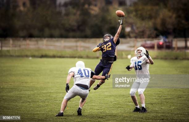 catching the ball on american football match! - quarterback stock photos and pictures