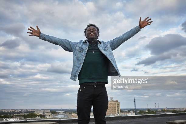 Catching the wind with arms outstretched. African man keeping balance on the roof