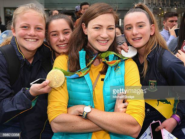 Cate Campbell poses with fans that hold her medals during the Australian Olympic Team Melbourne Welcome Home Celebration at Bourke Street on August...