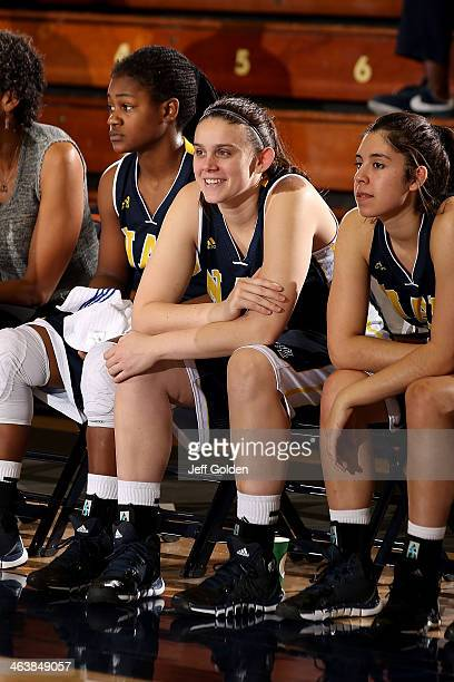Catelyn Preston of the Northern Arizona Lumberjacks smiles while seated on the bench next to teammates Brittani Lusain and Taylor Leyva during play...