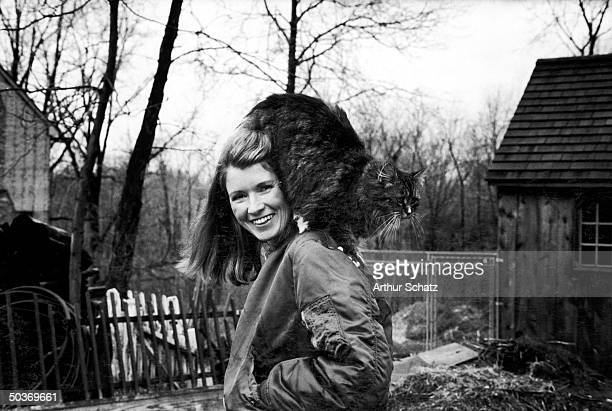 Caterer Martha Stewart outside in backyard with her pet persian cat perched on her shoulder