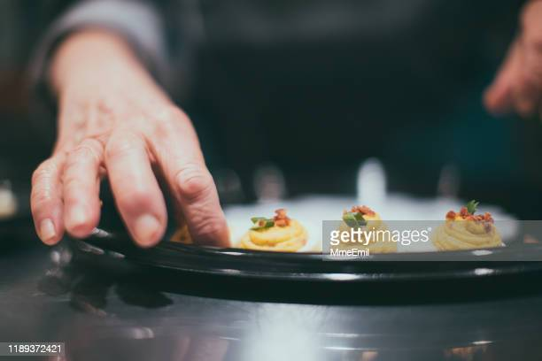 caterer placing deviled egg on a tray - mmeemil stock photos and pictures