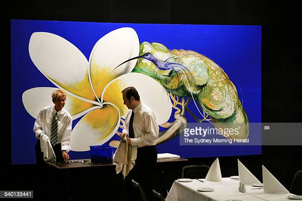 Caterers polish cutlery in front of a 1988 Brett Whiteley painting titled Hummingbird and Frangipani which is expected to fetch between $16 and $22...