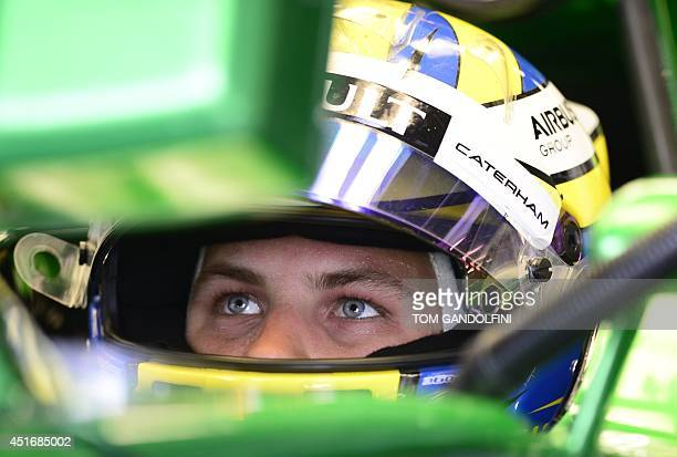Caterham F1 Team's Swedish driver Marcus Ericsson looks at a control screen in the pits during the second practice session at the Silverstone circuit...