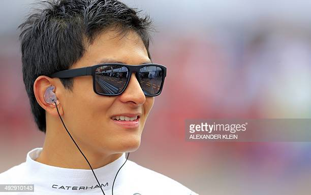 Caterham's Japanese driver Kamui Kobayashi looks on in the pits of the Monaco street circuit during the second practice session of the Monaco Formula...