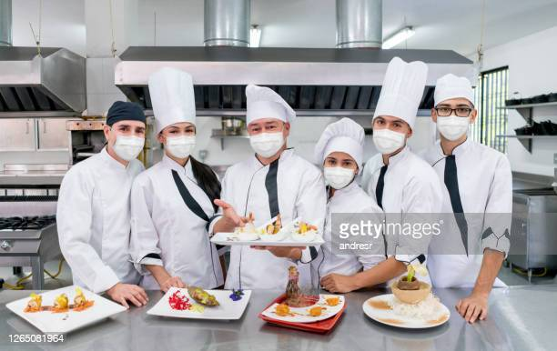 catering team wearing facemask in a commercial kitchen - biosecurity stock pictures, royalty-free photos & images