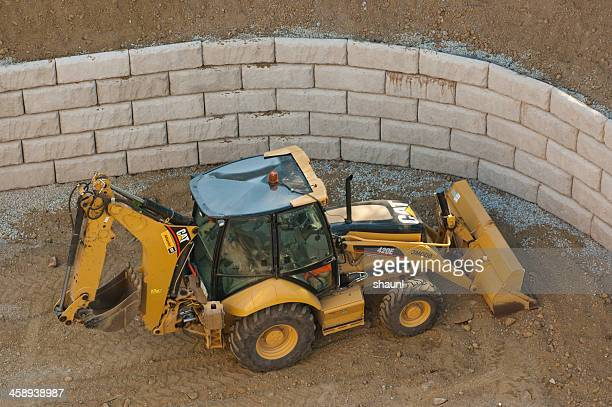 caterpillar backhoe - retaining wall stock pictures, royalty-free photos & images