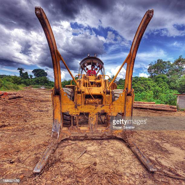 CONTENT] Caterpillar CAT 966C wheeled loader with wide open logging forks at a logging camp on Borneo island Old growth tropical rain forest is cut...